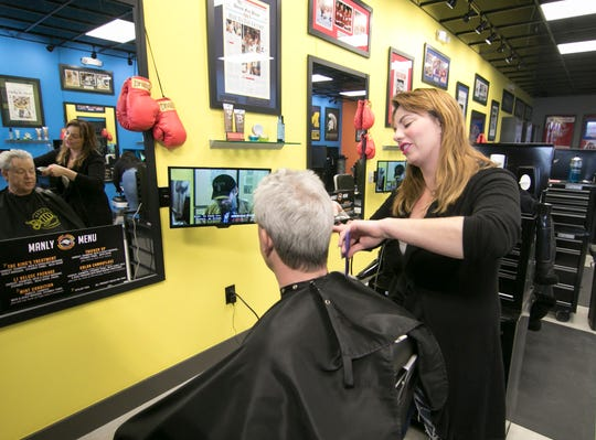 Lacey Campbell, manager of Lady Jane's Haircuts for Men in Brighton Twp., gives a trim to customer David Murphy on Grand River in Brighton.