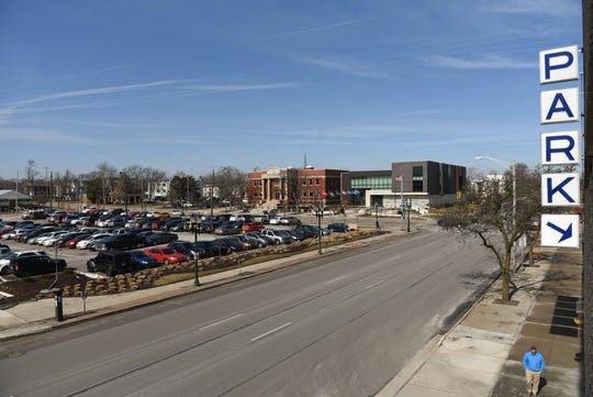 A Lansing Community College-owned surface lot (left) at the corner of West Shiawassee Street and North  Capitol Avenue in Lansing.  LCC officials want to build a five-story parking ramp there.
