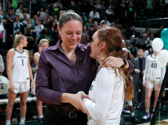 Michigan State's career assists leader Taryn McCutcheon, right, is congratulated by Kristin Haynie, who held the record previously, following a game against Penn State, Sunday, March 1, 2020, in East Lansing, Mich.