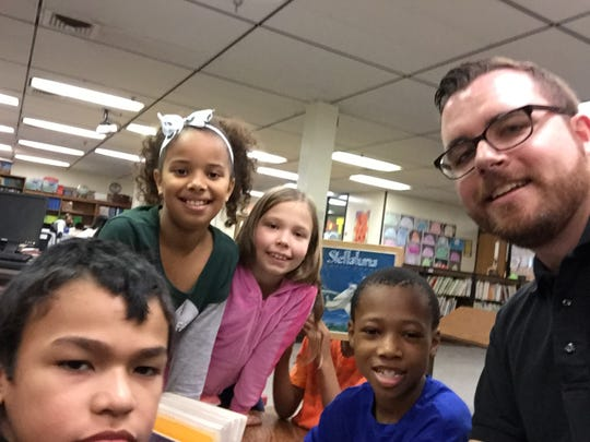 Matt Hund, LSJ engagement editor (right) grabs a selfie with kids during an #LSJreads day last year.