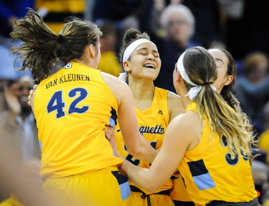 Marquette guard Selena Lott swarmed by teammates after hitting a long three-pointer at the halftime buzzer Sunday against DePaul.