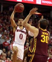 Wisconsin guard D'Mitrik Trice goes up for a basket as Minnesota forward Alihan Demir defends.
