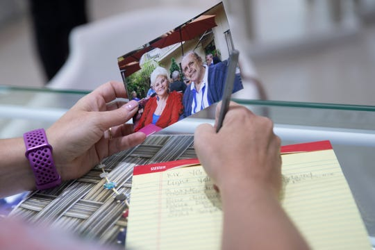 Dunkin's Diamonds floor manager Bobbi Dickson, takes notes as she looks over photos of Nancy and Kay Schumacher, Monday, March 2, 2020, at Dunkin's Diamonds in North Naples.