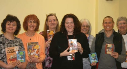 Not Your Mama's Book Group members holding books written by Cleo Coyle.