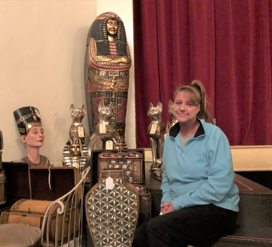 Christina Zayti sits near a few of the items that will go on sale beginning March 6.