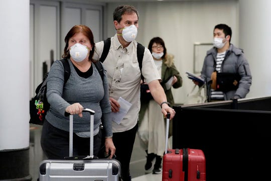 Travelers wear protective masks as they walk through terminal 5 at O'Hare International Airport in Chicago on, Sunday, March 1, 2020.
