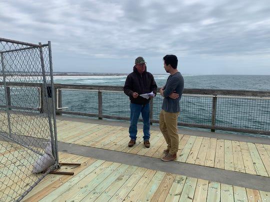 RJ Gorman Marine Construction supervisor Troy Sellars, left, talks with Navarre resident Dustin Bingham about selling him 20 pallets of the old Navarre Beach Fishing Pier wood.