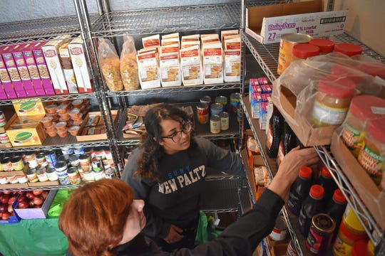 Serena Cruz, a sophomore and volunteer at the Student Christian Center Food Pantry at SUNY New Paltz, right, helps the food bank's director, the Rev. Dianna Smith, organize and refrigerate items on Friday, Feb. 28, in the Student Union