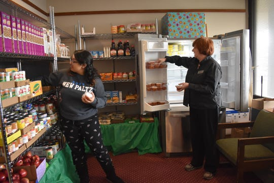Serena Cruz, a sophomore and volunteer at the Student Christian Center Food Pantry at SUNY New Paltz, left, helps the food bank's director, the Rev. Dianna Smith, organize and refrigerate items on Friday, Feb. 28,, in the Student Union.