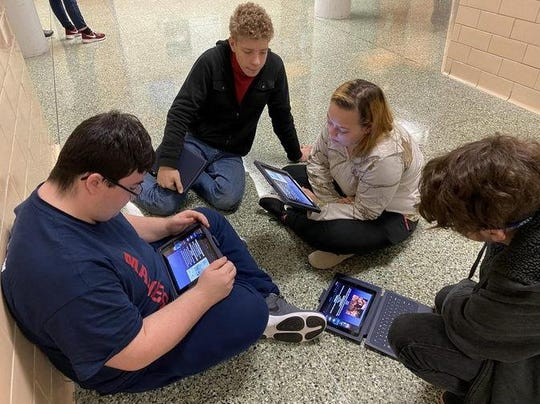 From left, Mike Carbaugh, Scott MacIntyre, Jazzman Patterson and Liam Hart sit in the hallway recently at Greencastle-Antrim High School and use their iPads to make a screen recording for a social-studies class presentation on the Reformation.