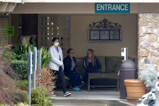 A person wearing a mask walks past a sign banning visitors at the Life Care Center in Kirkland, Wash., near Seattle, Monday, March 2, 2020. Dozens of people associated with the facility are reportedly ill with respiratory symptoms or hospitalized and are being tested for the COVID-19 virus. (AP Photo/Ted S. Warren)