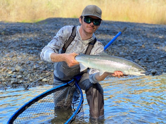 Ryan Tripp of Oroville holds a steelhead caught in southern Oregon while out with Dave Jacobs Professional Guide Service in late February. The fish was released to the water.