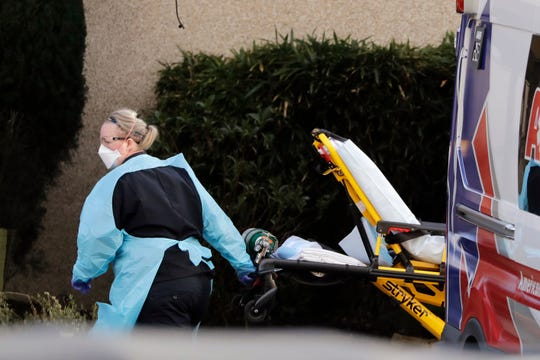 An ambulance worker wears protective equipment as she wheels a stretcher into a nursing facility where more than 50 people are sick and being tested for the COVID-19 virus Feb. 29, 2020, in Kirkland, Wash. Health officials reported two cases of COVID-19 virus connected to the Life Care Center of Kirkland. One is a Life Care worker, a woman in her 40s who is in satisfactory condition at a hospital, and the other is a woman in her 70s and a resident at Life Care who is hospitalized in serious condition. Neither have traveled out of the country.
