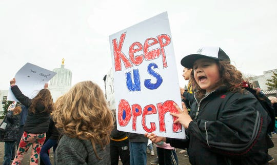 Uriah Garibay, 7, right, a second-grader at EAGLE Charter School holds a sign as students, teachers and parents from the school attend a rally at the Oregon State Capitol in Salem, March 2, 2020, urging officials to keep the school going. The school, a K-5 elementary school in Salem, serves more than 140 students from across the state. It was cited in a 2018 state audit that found glaring issues in how the school was being run.