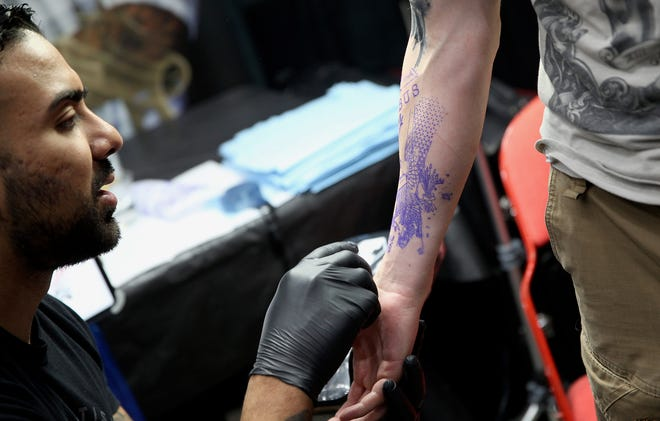 Joe Lucero, left, checks the tattoo pattern on Gus Costas' arm, right, at the West Texas Tattoo Convention at the Foster Coliseum in San Angelo.