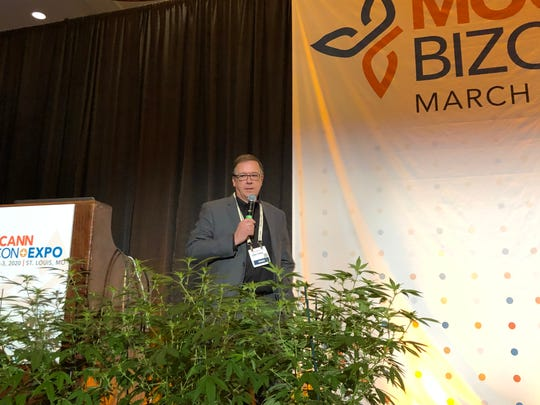 Flanked by hemp plants, Lyndall Fraker, director of Missouri's medical cannabis program, gives a keynote speech at MoCannBizCon+Expo in St. Louis on Monday, March 2, 2020.