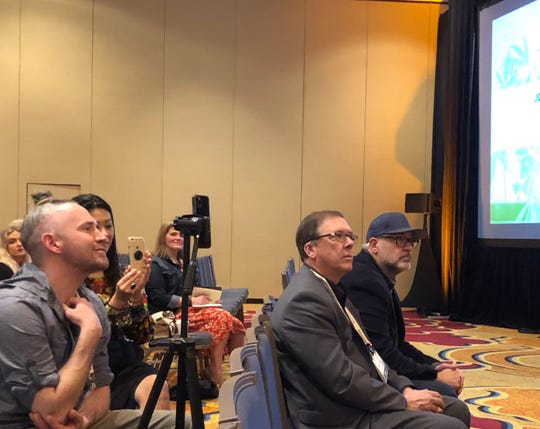 Lyndall Fraker (in suit jacket), director of Missouri's medical cannabis program, sits with Andrew Mullins (with blue ballcap), executive director of the Missouri Medical Cannabis Trade Association, at the MoCannBizCon+Expo in St. Louis on Monday, March 2, 2020.