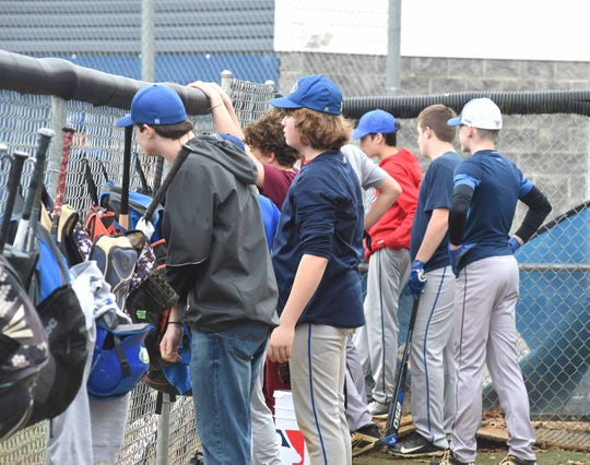Players hoping to make the junior varsity team gather at the fence in the third base dugout to await their turn at bat during a practice the first week of the spring season.