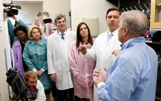 From left, Deputy Secretary for Health Dr. Shamarial Roberson, State Senator State Senator Janet Cruz, State Surgeon General Dr. Scott Rivkees, Lieutenant Governor Jeanette Nuñez, Governor Ron DeSantis, looks on while Andrew Cannons, Laboratory Director at the Bureau of Public Health Laboratories explains the testing procedures of potential coronavirus cases at the Florida Department of Health Laboratory in Tampa, Florida on Monday, March 2, 2020.