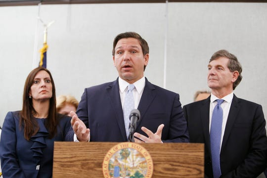 Lieutenant Governor Jeanette Núñez, left, and State Surgeon General Dr. Scott Rivkees, looks on while Florida Gov. Ron DeSantis speaks about the confirmed coronavirus cases in the state at the Florida Department of Health Laboratory in Tampa on March 2, 2020.