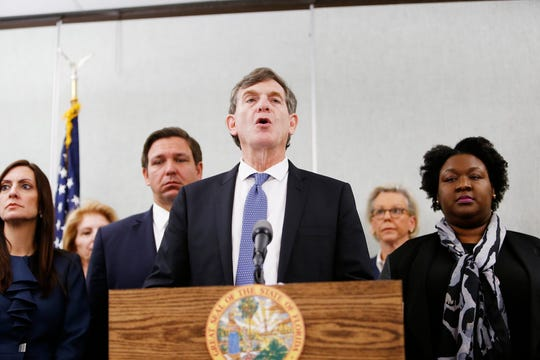 (From left) Florida Lieutenant Governor Jeanette Nuñez, left, Florida Governor Ron DeSantis, looks on while State Surgeon General Dr. Scott Rivkees, center, speaks about the confirmed coronavirus cases in Hillsborough and Manatee Counties while Mayor of Tampa Jane Castor (standing in the rear), Deputy Secretary for Health Dr. Shamarial Roberson, right, along with other local and state officials are in attendance during a press conference at the Florida Department of Health Laboratory in Tampa, Florida on March 2, 2020.