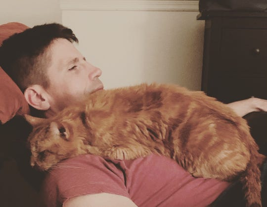 """Oliver, a 16-year-old orange tabby, sleeps on the chest of his """"buddy"""" Luke Latham, of Stuart. Latham and his wife, Christine, adopted Oliver as part of Dogs & Cats Forever's fospice program, which enables terminally ill or elderly cats to live out the rest of their lives in a home rather than in the shelter."""