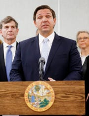 Florida Governor Ron DeSantis, center, speaks about the confirmed a coronavirus cases in Hillsborough and Manatee Counties while State Surgeon General Dr. Scott Rivkees, left, Mayor of Tampa Jane Castor, right, along with other local and state officials who are in attendance during a press conference at the Florida Department of Health Laboratory in Tampa, Florida on March 2, 2020.(Octavio Jones/Tampa Bay Times via AP)