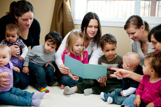 A group of mothers with their infants and toddlers enjoying story time.