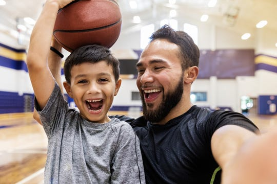A father laughs and takes a selfie while his son holds a basketball on his head.