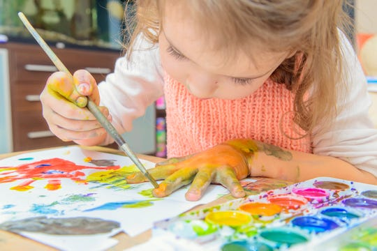 A girl draws and paints on paper and her hands.