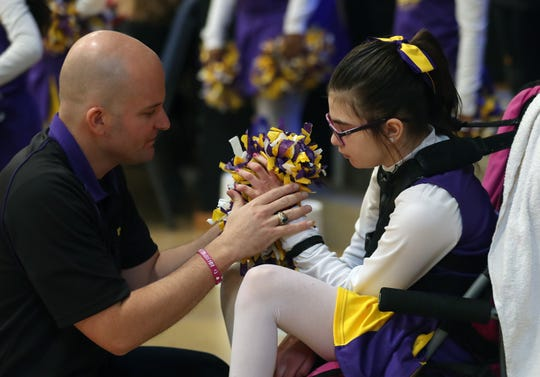Chad Cunningham helps his daughter Keira, fasten her pom poms during a basketball game that she was cheering in with her Upward squad at Gracepoint Gospel Fellowship in New City Feb. 29, 2020. Kiki suffered a brain hemorrhage and stroke at age 8, and is now recovering at home.
