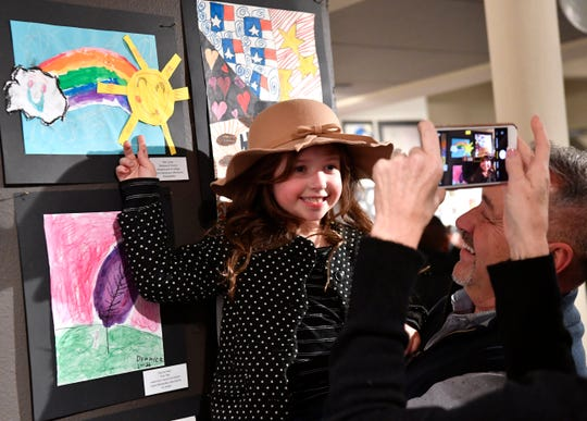 Randy Turner holds his six-year-old granddaughter Ellie beside her artwork Feb. 20, 2020. Ellie is a kindergartener at Taylor Elementary, Youth Art Month features hundreds of original art pieces by Big Country students.