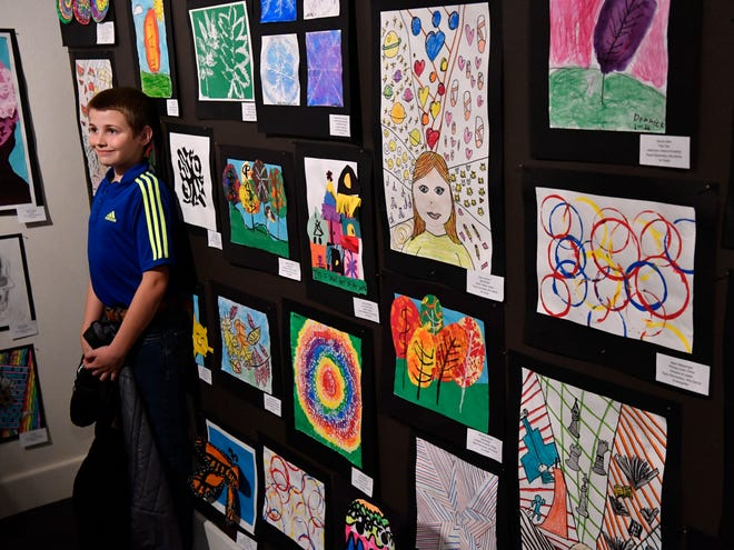 Evan Chaney, 10 and a 4th grade student at Taylor Elementary, stands beside his artwork as his mother Michelle photographs him Feb. 20, 2020. Youth Art Month at the Grace Museum features hundreds of original art pieces by Big Country students.