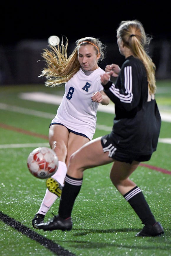 Roberson's Harper Boatwright kicks a ball past Asheville's Olivia Slatton during their game at Asheville High School on March 2, 2020.