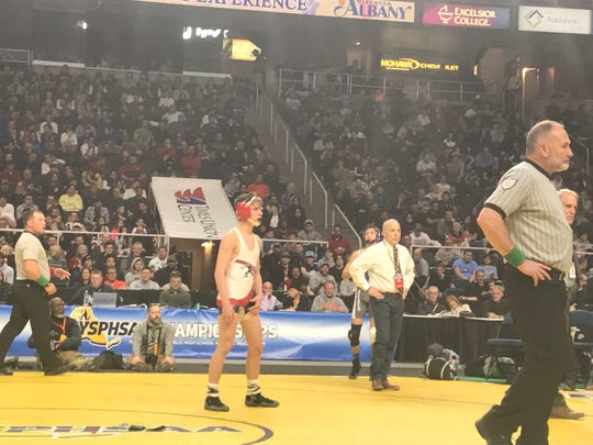 Chenango Forks' Tyler Ferrara looks on Saturday night at Albany's Times Union Center as officials determine whether he had just won a 106-pound state title. A stalling point awarded to Ferrara late in regulation was overturned and he wound up losing, 6-4 in overtime to Bay Shore's Elijah Rivera.