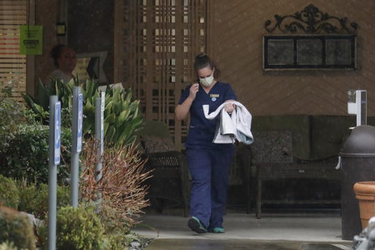 A worker at the Life Care Center in Kirkland wears a mask as she leaves the building, Monda. Several of the people who have died in Washington state from the COVID-19 coronavirus were tied to the long-term care facility, where dozens of residents were sick.