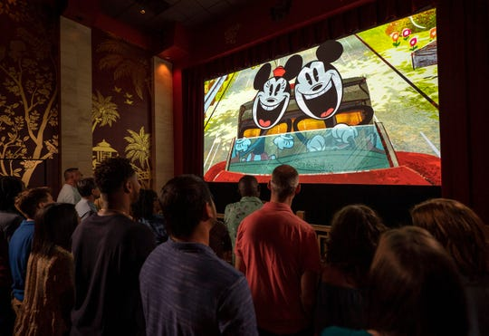 """Guests watch a new """"Mickey Mouse"""" cartoon short, """"Perfect Picnic,"""" to begin their Mickey & Minnie's Runaway Railway experience in Disney's Hollywood Studios at Walt Disney World Resort in Lake Buena Vista, Fla. The first ride-through attraction in Disney history featuring Mickey Mouse and Minnie Mouse brings guests into the vibrant world of """"Mickey Mouse"""" cartoon shorts."""