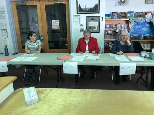 Volunteers sit at the entry the polling station at Westford School hand ballots to voters on Town Meeting Day, March 3, 2020.