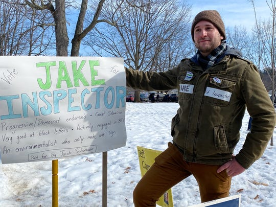 Jake Schumann poses next to his campaign sign at the Robert Miller Community and Recreation Center in Burlington on Town Meeting Day, March 3, 2020.