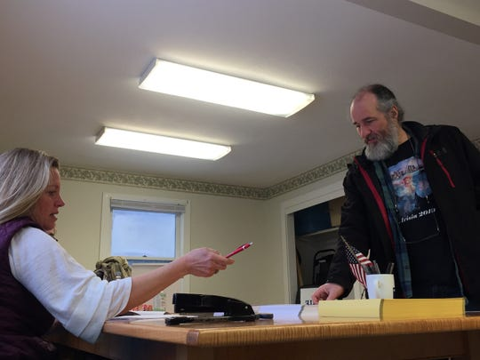 St. George resident Tim Dartt talks with Town Clerk April Pillsbury as he prepares to vote in the presidential primary at the town offices on March 3, 2020.