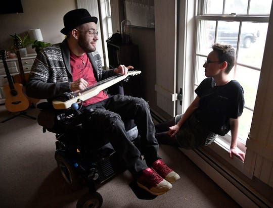 """Ryan """"Gooch"""" Nelson plays a song from his latest album """"Outside the Window"""" while his fiancee Brianna Bowers listens, at their home in Pilesgrove. Gooch was in a car accident 16 years ago that left him a quadriplegic."""