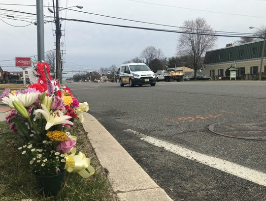 Flowers line a curb near the scene of a pedestrian's death on Kings Highway in Cherry Hill.