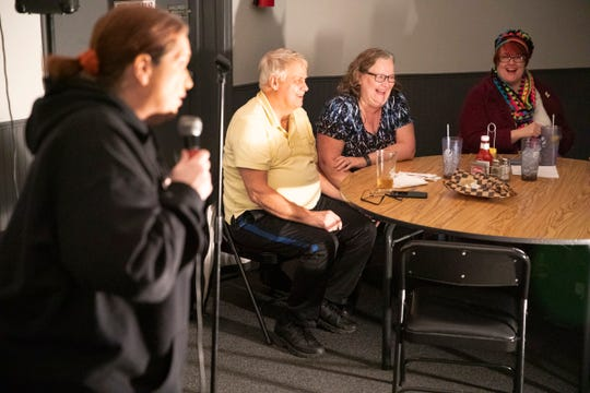 Audience members Pete and Becky Dolan and Rebecca Pope laugh as Lori Graves tries out her new material about dating in her 40s at an open mic night event the Dock at Water gathering place on Feb. 13, 2020, in Chillicothe, Ohio.