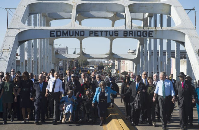 President Barack Obama, first lady Michelle Obama, former president George W. Bush, Laura Bush and Rep. John Lewis, D-Ga., lead a new march across the Edmund Pettus Bridge on March 7, 2015 to mark 50 years since the Selma-to-Montgomery civil rights marches.