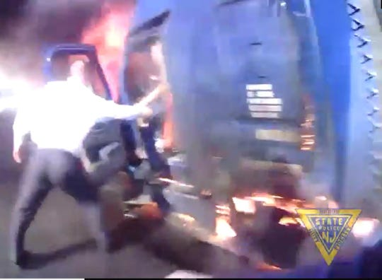 A still image from New Jersey State Trooper Robert Tarleton's body camera shows State Police Lt. Edward Ryer pulling a man from a burning tractor-trailer on I-287 in Bridgewater. The truck exploded as Tarleton and Ryer moments after they pulled the man from the truck on March 2, 2020.