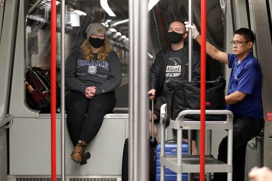 Travelers Meredith Ponder, left, and Coleby Hanisch, both of Des Moines, Iowa, wear masks to remind them not to touch their faces as they ride a train at Seattle-Tacoma International Airport on Tuesday in Washington state.