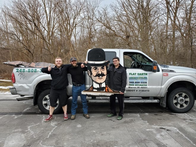 Christopher Charbonneau, center, purchased the 25-foot Gibraltar Trade Center sign. His employees, Benjamin Galdys and Mark Pawlicki, left and right, helped him take it home.
