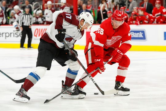 Detroit Red Wings defenseman Gustav Lindstrom (28) takes the puck from Colorado Avalanche center Tyson Jost (17) in the third period of an NHL hockey game Monday, March 2, 2020, in Detroit. (AP Photo/Paul Sancya)