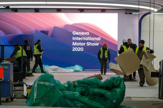 Workers dismantle a booth on Friday after the Geneva auto show was canceled because of the coronavirus. Ford and Fiat Chrysler are restricting nonessential employee air travel, both domestic and international. And GM is screening all visitors at facilities.