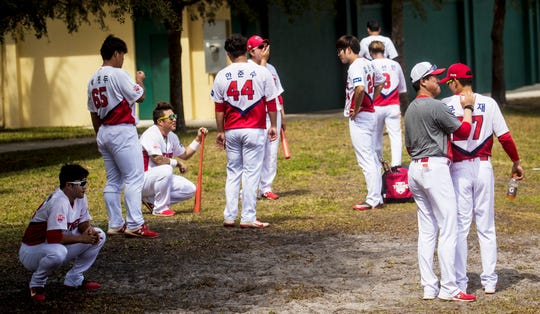 Members of the Kia Tigers, a professional baseball team from South Korea, warm up and congregate outside of the dugout at Terry Park in Fort Myers while playing a spring training game against a baseball scouting league team on Tuesday, March 3, 2020. The team is delaying its departure back to South Korea because of the coronavirus. They are scheduled to head back on the 15th but that could change depending on the outbreak.